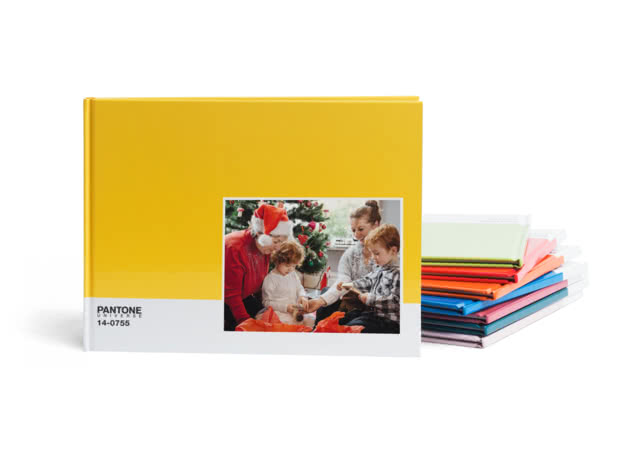 Bright yellow A4 Pantone book with family photo on the cover and other books stacked behind